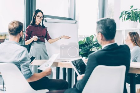 young asian businesswoman giving presentation to multiracial colleagues in conference hall
