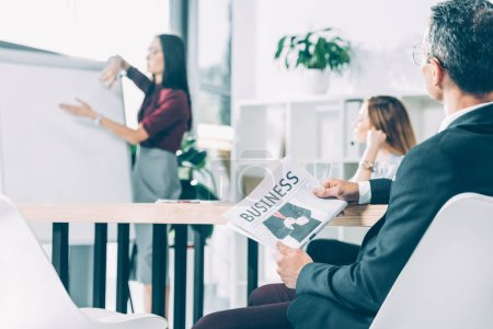 businessman holding newspaper and listening to presentation in conference