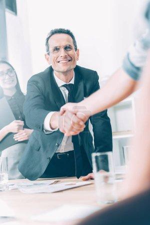 partenaires commerciaux se serrant la main dans le bureau moderne