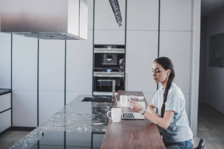 side view of beautiful freelancer working at laptop and holding smartphone in kitchen