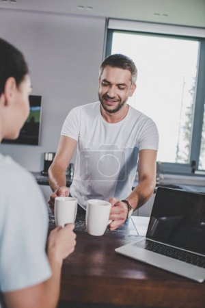smiling boyfriend giving cup of coffee to girlfriend in kitchen