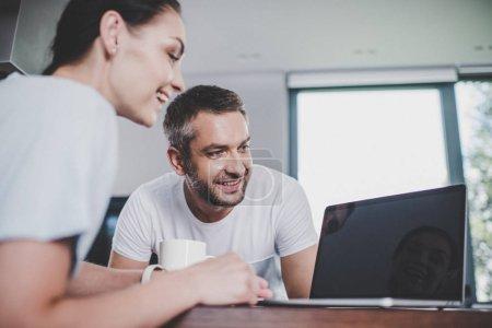 Photo pour Couple souriant regardant ordinateur portable avec écran blanc dans la cuisine - image libre de droit