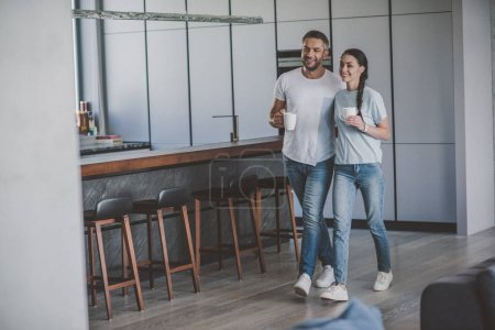 Photo for Smiling couple with coffee cups in kitchen at home - Royalty Free Image