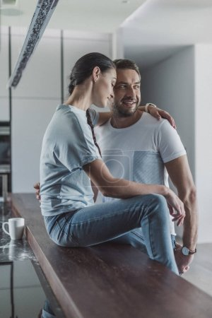 Photo for Smiling couple embracing each other in kitchen at home - Royalty Free Image