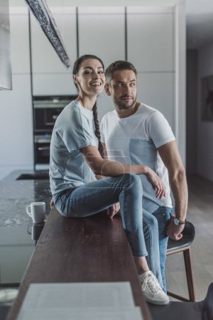 happy young woman sitting on kitchen counter while her boyfriend standing near at home