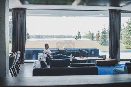 vue distante du mâle pigiste travaillant avec ordinateur portable sur le sofa à la maison