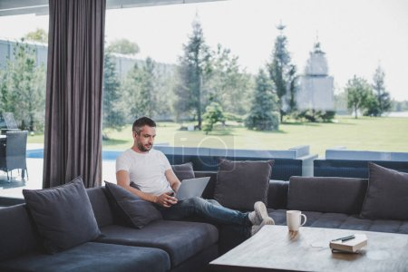 focused adult male freelancer working with laptop on sofa at home