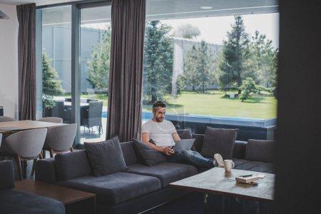 mise au point sélective des mâle pigiste travaillant avec ordinateur portable sur le sofa à la maison