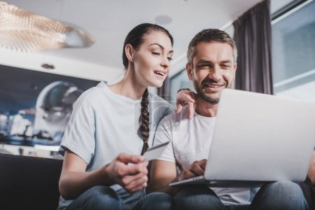 smiling couple with laptop doing online shopping by credit card at home