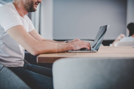 Photo for Partial view of male freelancer using laptop with blank screen at home - Royalty Free Image