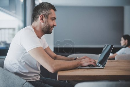 side view of smiling male freelancer using laptop with blank screen at home