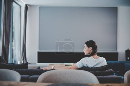side view of beautiful smiling woman resting on couch at home