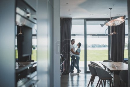 distant view of handsome adult man embracing attractive girlfriend at home