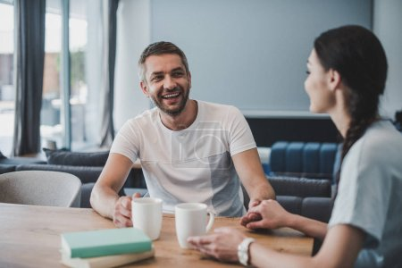 laughing man holding hands of girlfriend at table with coffee and books at home