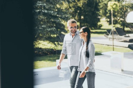 smiling couple in sunglasses walking at country house