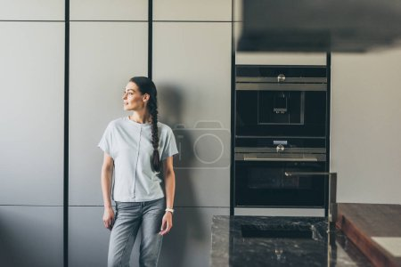 attractive young woman looking away in kitchen at home