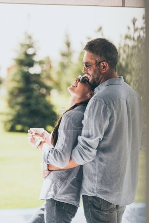 selective focus of man in sunglasses embracing girlfriend with coffee cup outdoors
