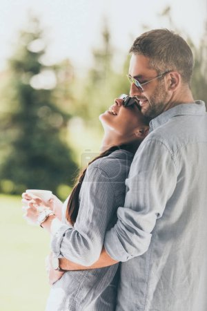 Photo for Side view of happy man in sunglasses embracing girlfriend with coffee cup outdoors - Royalty Free Image