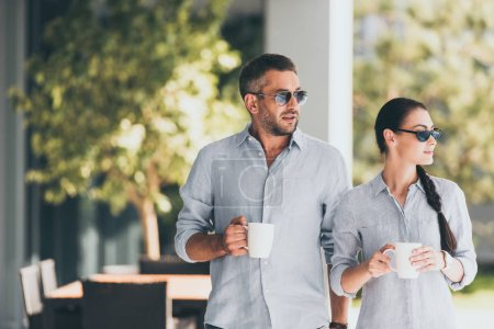 selective focus of couple in sunglasses with coffee cups at country house