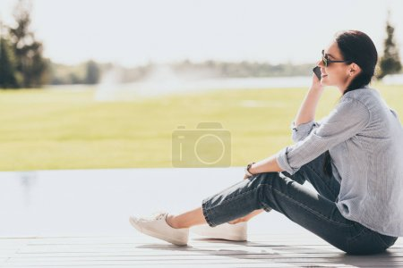 selective focus of happy woman in sunglasses talking on smartphone outdoors
