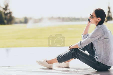 Photo for Selective focus of happy woman in sunglasses talking on smartphone outdoors - Royalty Free Image