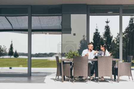 Photo for Couple in sunglasses with coffee cups talking at table at country house - Royalty Free Image