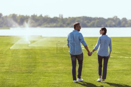 Photo for Couple in sunglasses holding hands and looking at each other at lawn outdoors - Royalty Free Image