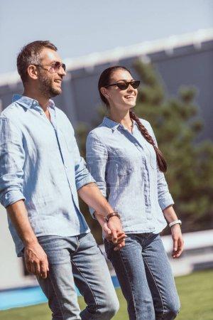 Foto de Pareja feliz en gafas de sol cogidos de la mano y caminando al aire libre - Imagen libre de derechos