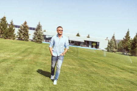 handsome adult man in sunglasses walking with hands in pockets on lawn near country house