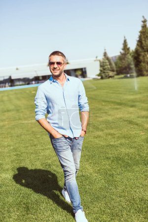 smiling adult man in sunglasses walking with hands in pockets on grass near country house