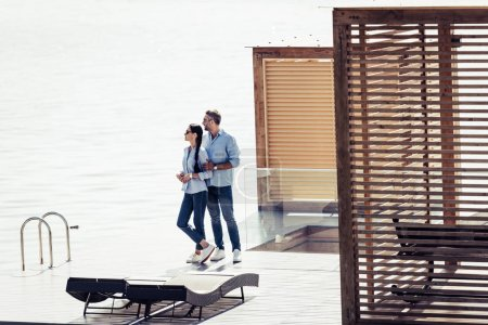 stylish couple standing on pier near lake at country house
