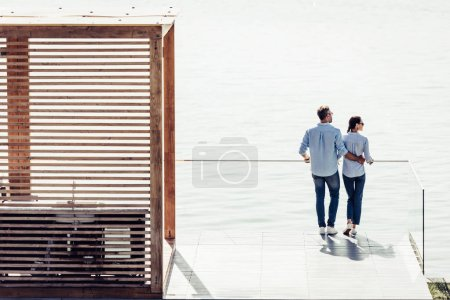 high angle view of stylish couple standing on pier near lake at country house
