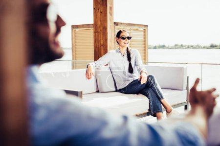 selective focus of smiling woman in sunglasses on sofa while her boyfriend sitting near at country house