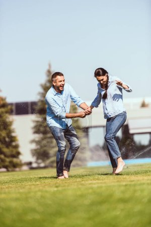 adult laughing man holding hand of girlfriend and having fun with automatic watering on green lawn near country house