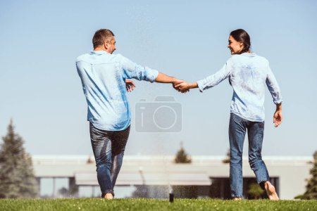 rear view of couple holding hands and dancing under automatic watering on green lawn near country house