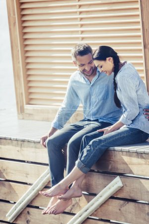 smiling adult man embracing girlfriend on wooden pier