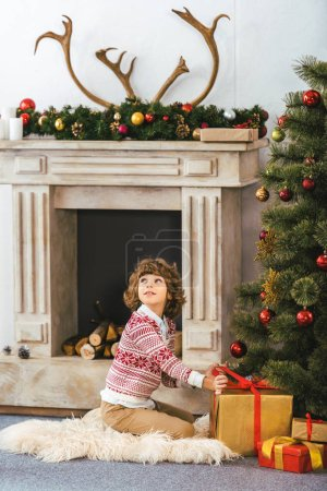 adorable happy kid sitting on floor with christmas gift boxes and looking up