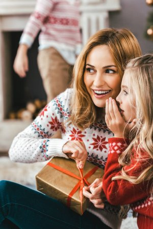 mother and daughter gossiping and unpacking gift together while sitting on floor