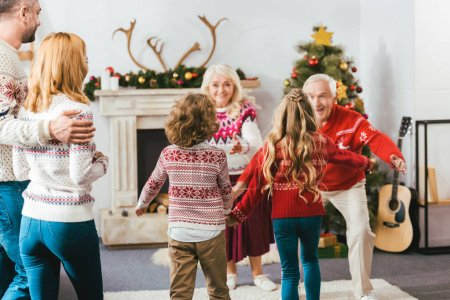 rear view of kids running to hug grandparents during christmas eve at home