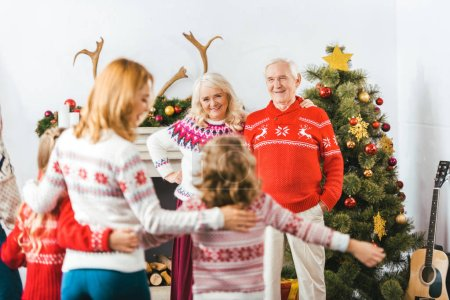 happy grandparents looking at daughter with grandkids at home during christmas