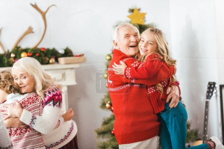 happy grandparents embracing with kids on christmas at home