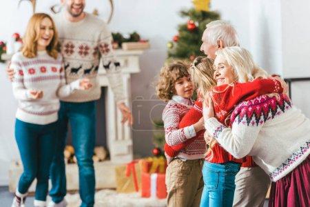 Photo pour Grands-parents embrasser avec les enfants pendant la veille de Noël à la maison - image libre de droit