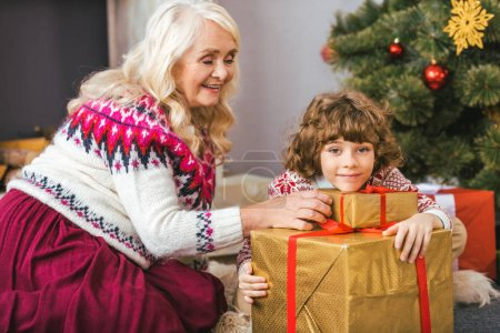 happy grandmother and her grandson with christmas gifts looking at camera