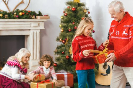 grandparents and adorable kids with gift boxes spending time together on christmas