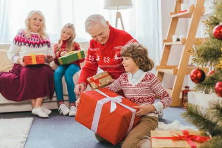 grandparents and kids with gift boxes spending time together on christmas