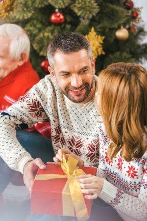 Photo pour Beau jeune homme présentant cadeau de Noël à sa femme - image libre de droit