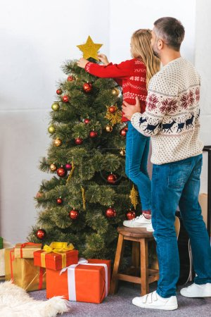 handsome father carrying his daughter while she decorting christmas tree