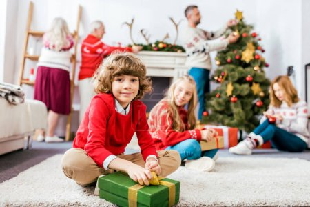 smiling siblings sititng on floor together with gifts during christmas eve