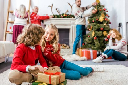 happy siblings sititng on floor together with gifts during christmas eve