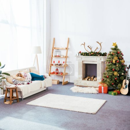 Photo for Young woman sleeping on couch in christmas decorated living room - Royalty Free Image
